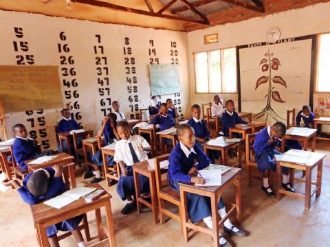 Children wearing school uniforms seated at desks in classroom