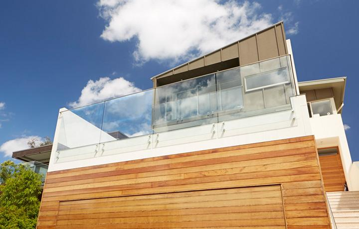 Contemporary style two story home lit by bright sunlight and blue sky with clouds in background