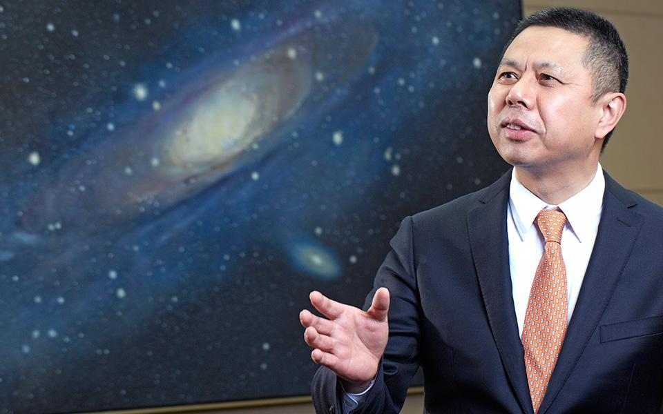 Jifan Gao speaking with backdrop of Milky Way galaxy