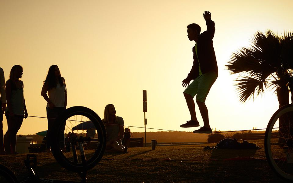 Silhouetted children playing on beach with sun in background