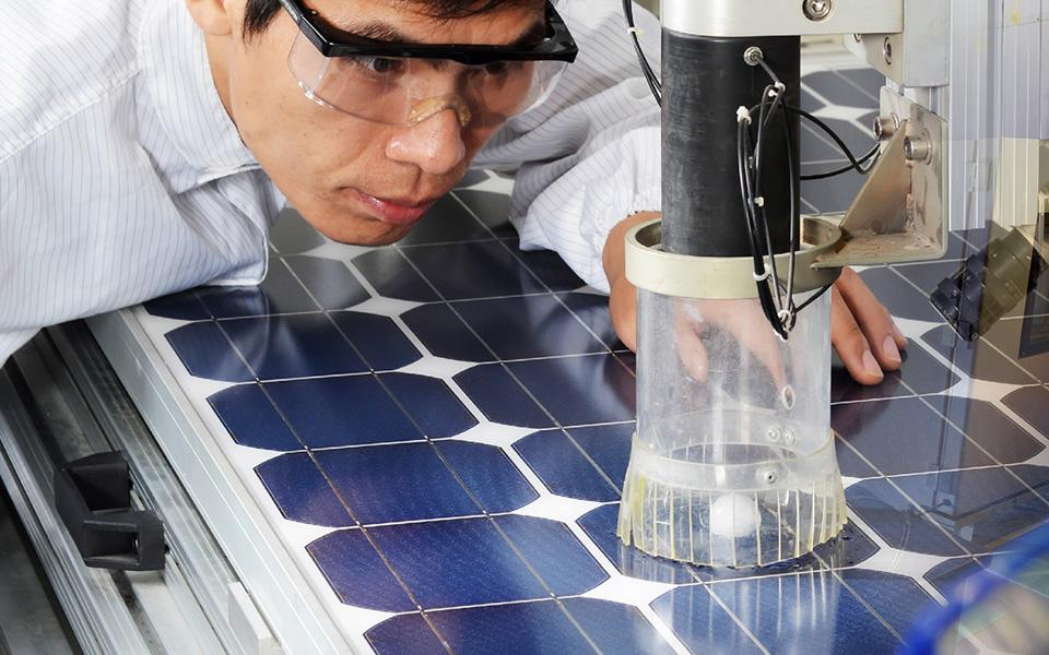 Scientist wearing goggles looks at lab equipment over solar cells