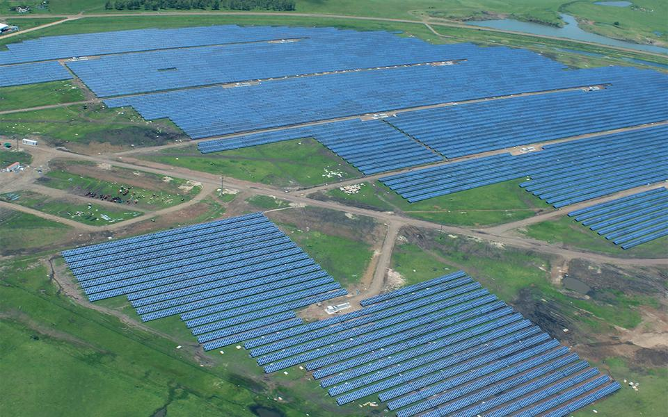 Aerial view of large-scale utility solar installation on flat landscape
